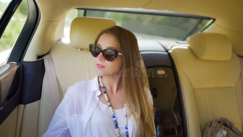 在昂贵的汽车的愉快的富有的女孩骑马,豪华生活方式,暑假 免版税库存照片