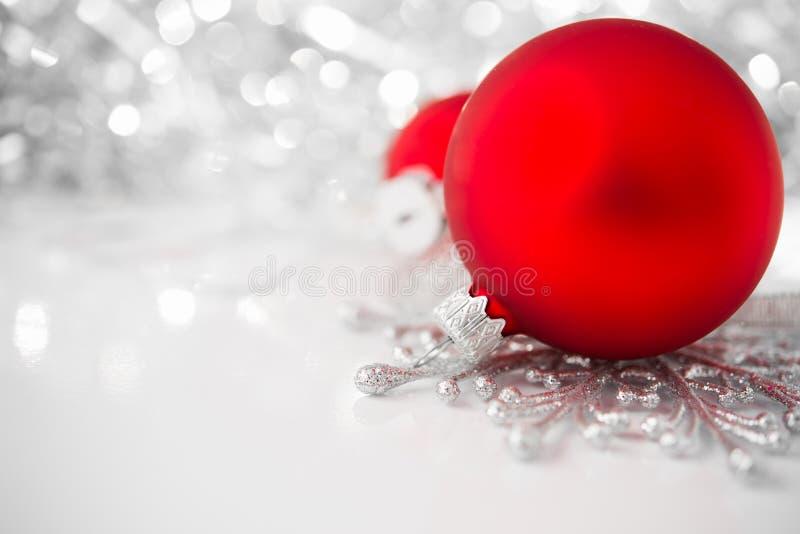 在明亮的假日背景的红色和银色xmas装饰品 图库摄影