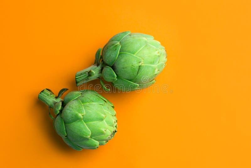 在明亮的坚实橙色背景的成熟绿色朝鲜蓟 创造性的食物海报 r 地中海西班牙烹调 免版税图库摄影