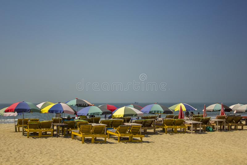 在明亮的多彩多姿的阳伞下的木黄色海滩懒人在反对海的沙子在一清楚的天空蔚蓝下 免版税库存图片