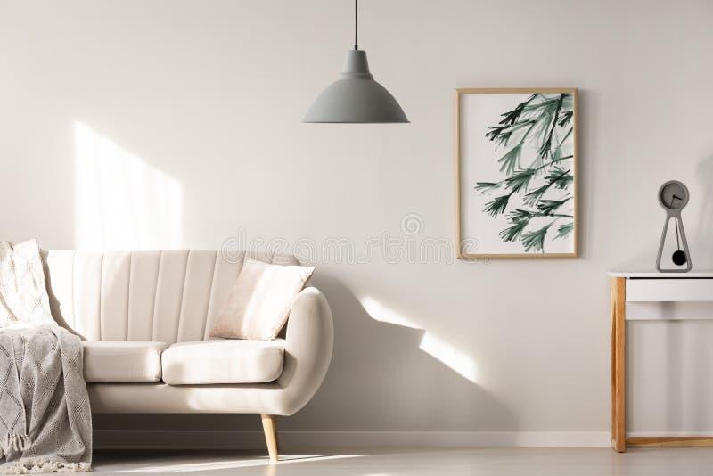 在明亮的客厅内部的灰色灯与在bei旁边的海报 免版税库存照片