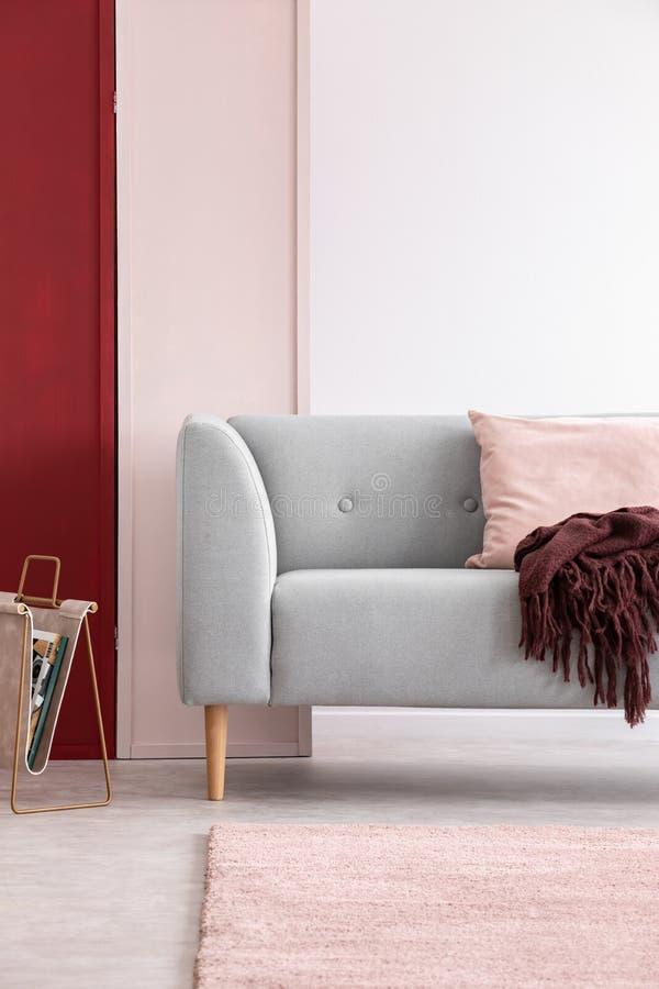在明亮的客厅内部的灰色长沙发与三色的墙壁,真正的照片 免版税图库摄影