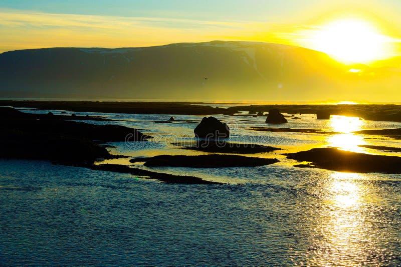 在明亮的日落的看法停泊与山背景boulers和小岛的剪影和阴影的风景 免版税库存图片