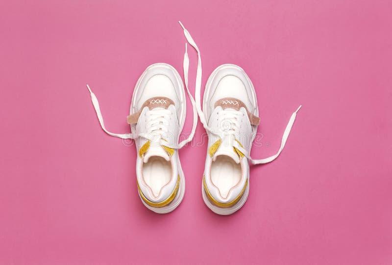 在明亮的桃红色背景的白色女性运动鞋 时尚博克或杂志概念 妇女的鞋子,时髦运动鞋 库存照片