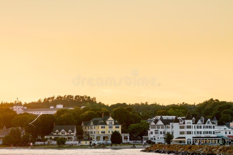 在明亮的桔子和黄色日落期间的街市Mackinac海岛 免版税库存照片