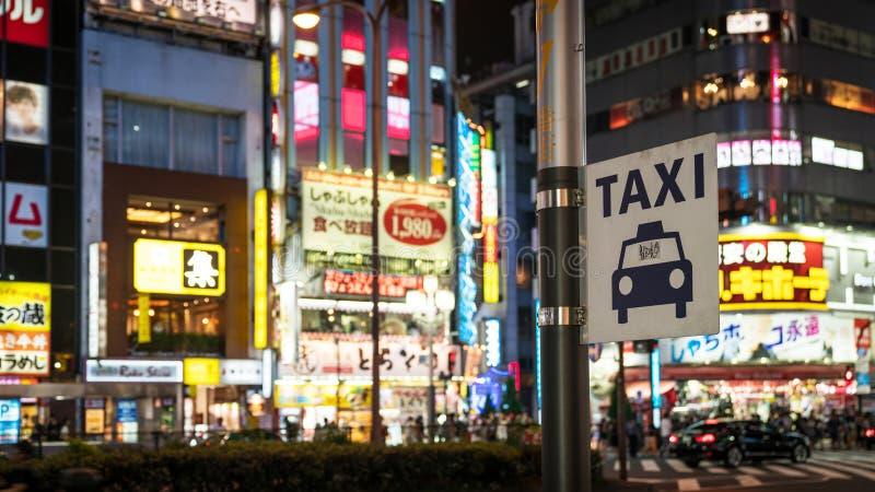 在明亮的氖和广告光下的出租汽车标志在Kabukicho在新宿,东京,日本 库存图片