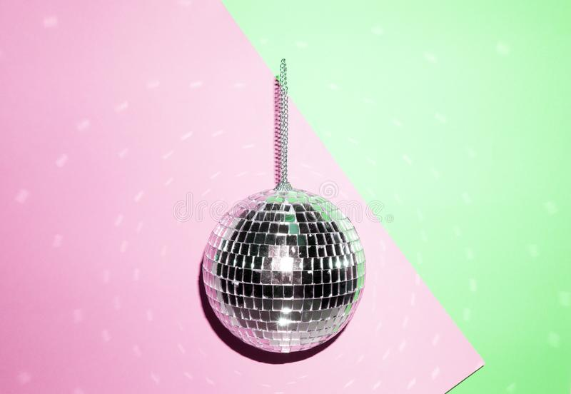在明亮的淡色创造性的背景的发光的迪斯科球 流行音乐迪斯科音乐样式属性80 免版税库存照片