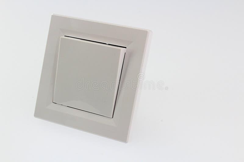 在明亮的背景的简单的长方形乳脂状的色的墙壁光摇臂开关 免版税图库摄影