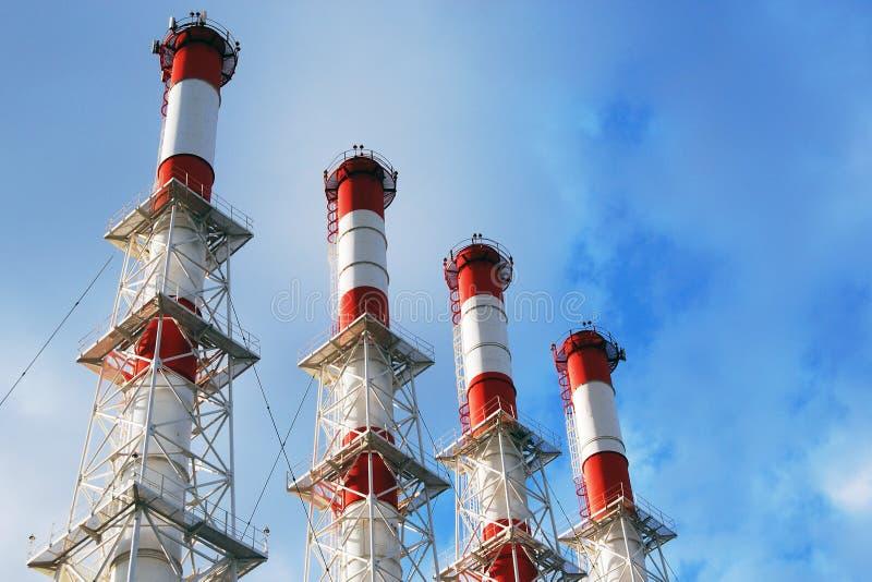 在明亮的蓝色多云天空的四个工厂管子 免版税库存图片
