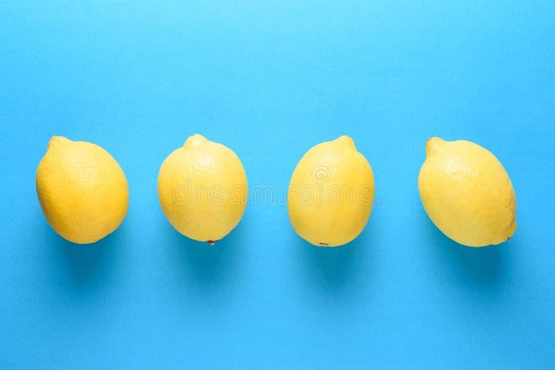 在明亮的蓝色背景的新鲜的柠檬 夏天最小的概念 免版税图库摄影