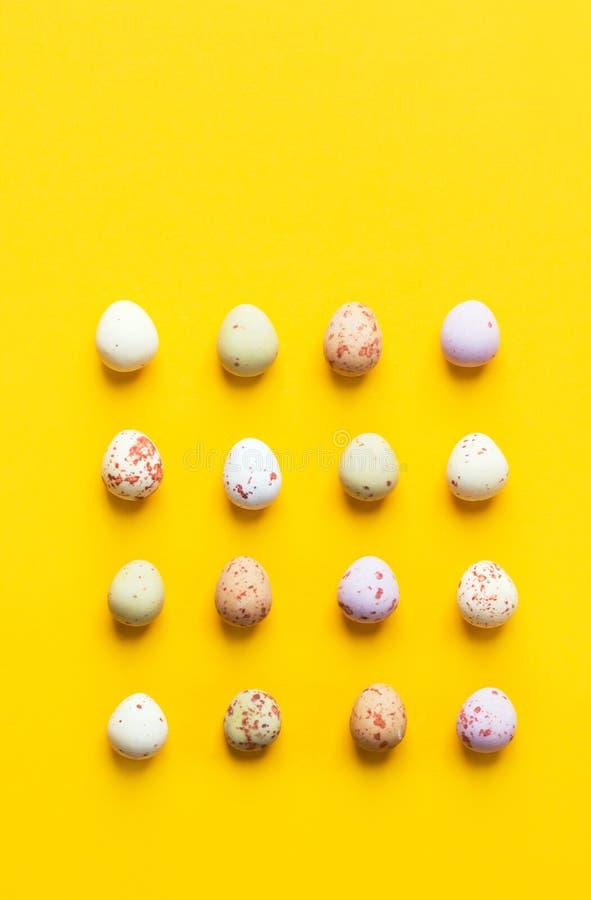 在明亮的黄色背景的图表knolling的样式安排的多彩多姿的有斑点的朱古力蛋 E 图库摄影