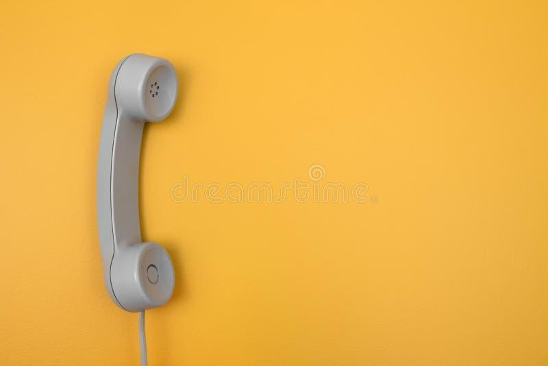 在明亮的黄色背景的经典受话器 免版税库存图片
