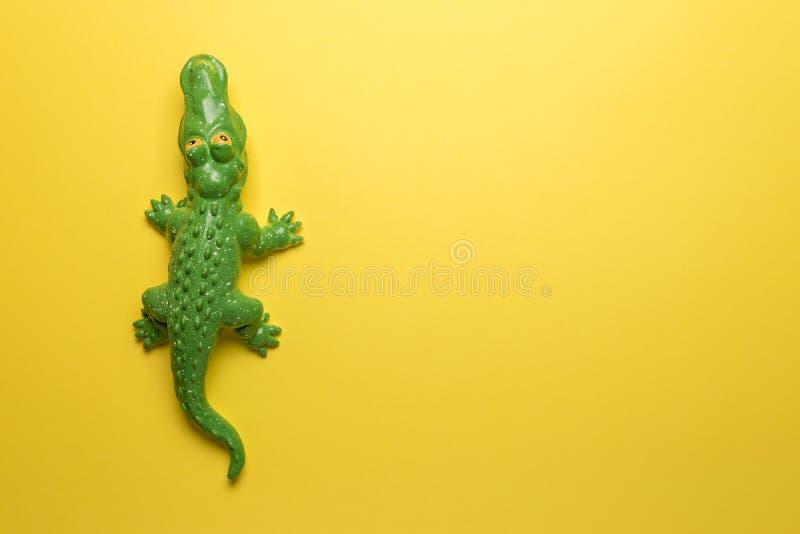 在明亮的黄色背景的绿色鳄鱼玩具 r 图库摄影