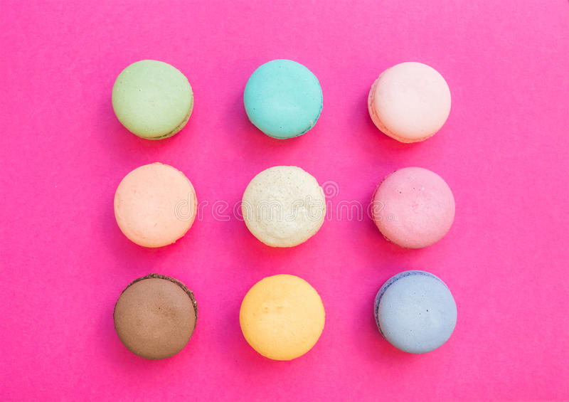 在明亮的紫红色的桃红色背景的甜五颜六色的法国蛋白杏仁饼干饼干 免版税库存照片