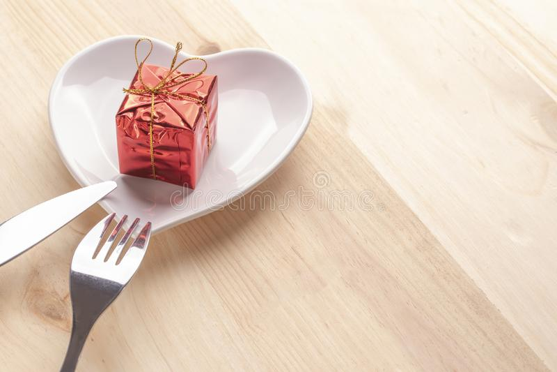 在明亮红色包装的一件礼物在以心脏的形式一块白色板材在与叉子和刀子的木背景 库存图片