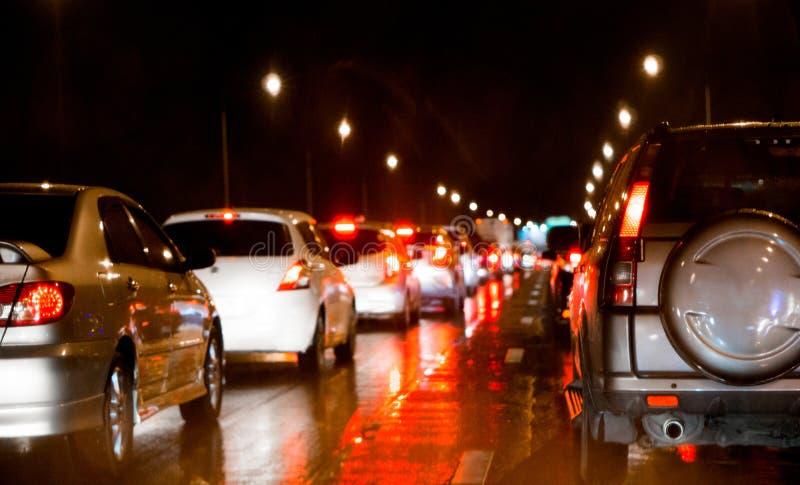 在明确方式和汽车刹车灯的被弄脏的堵车在曼谷,夜和拷贝空间的泰国 免版税图库摄影