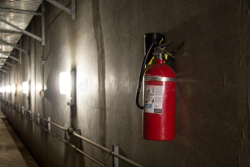 在昏暗地被点燃的走廊的灭火器 免版税库存图片