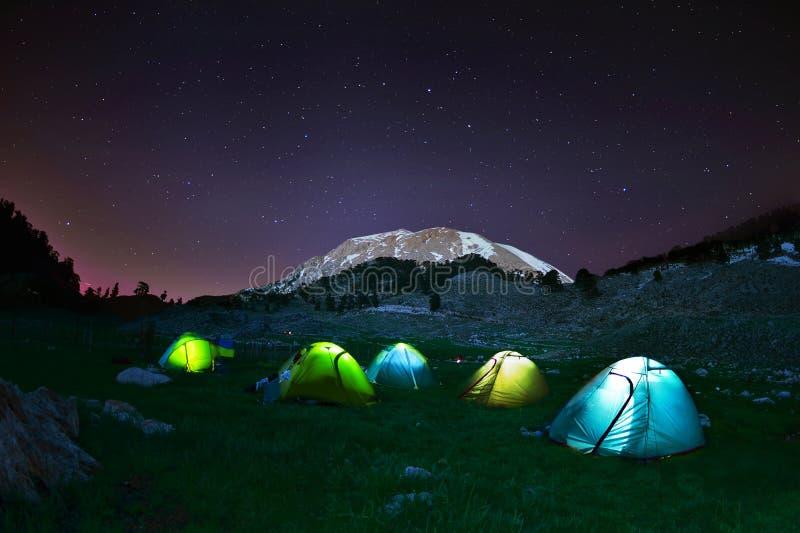在星下的有启发性黄色野营的帐篷在晚上 库存照片