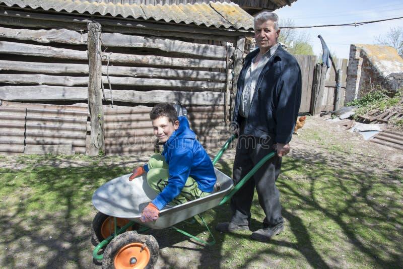 在春天在庭院祖父滚动他的孙子  库存图片