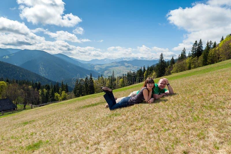 在春天在背景的草的少妇和人  免版税图库摄影