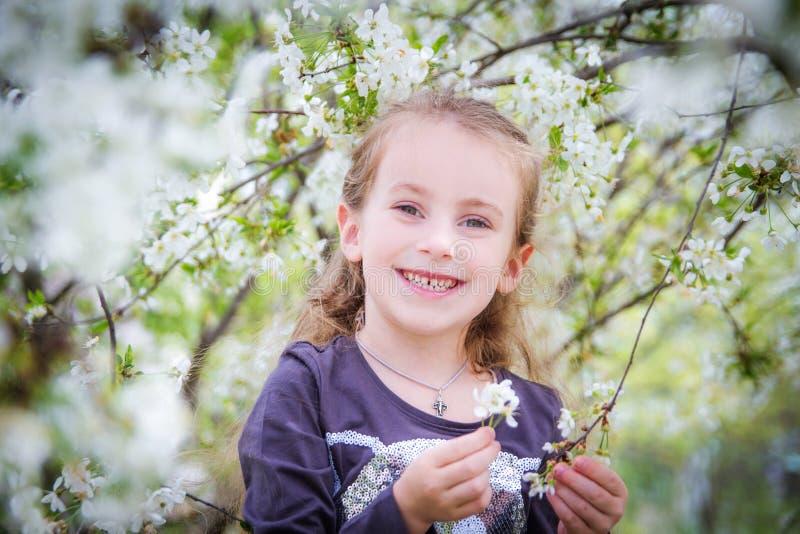 在春天开花树中的逗人喜爱的女孩 库存照片