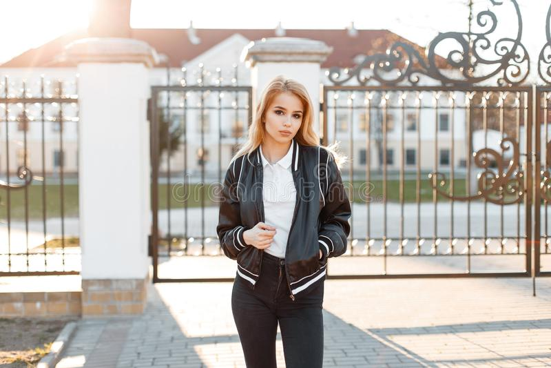 在春天时髦的夹克的有吸引力的年轻女人模型在白色衬衫姿势的时髦牛仔裤在葡萄酒门附近 库存图片