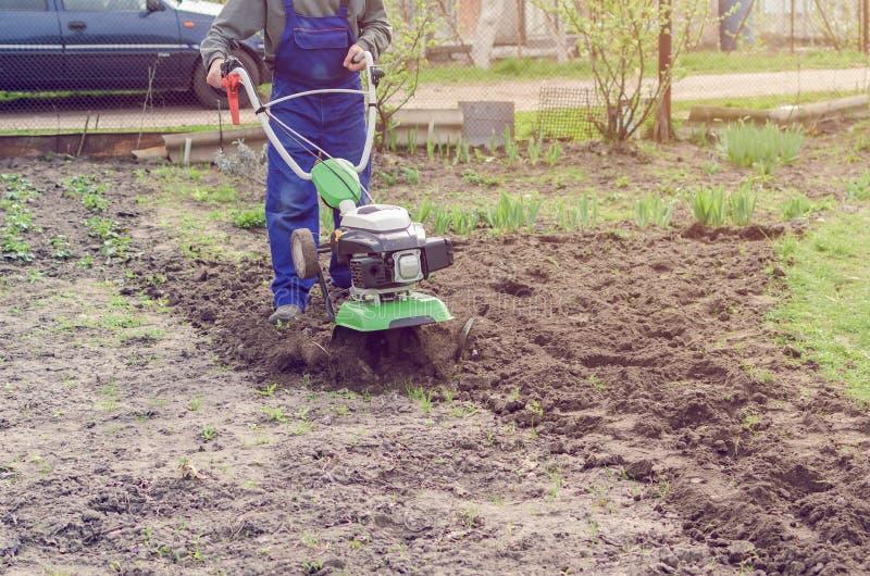 在春天有翻土机机器的庭院供以人员工作 库存图片