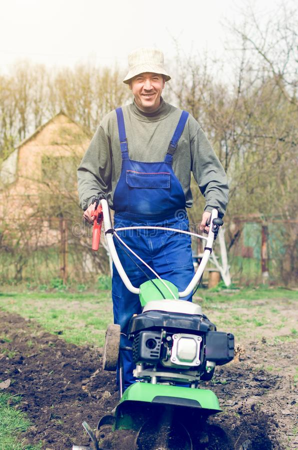 在春天有翻土机机器的庭院供以人员工作 免版税库存图片