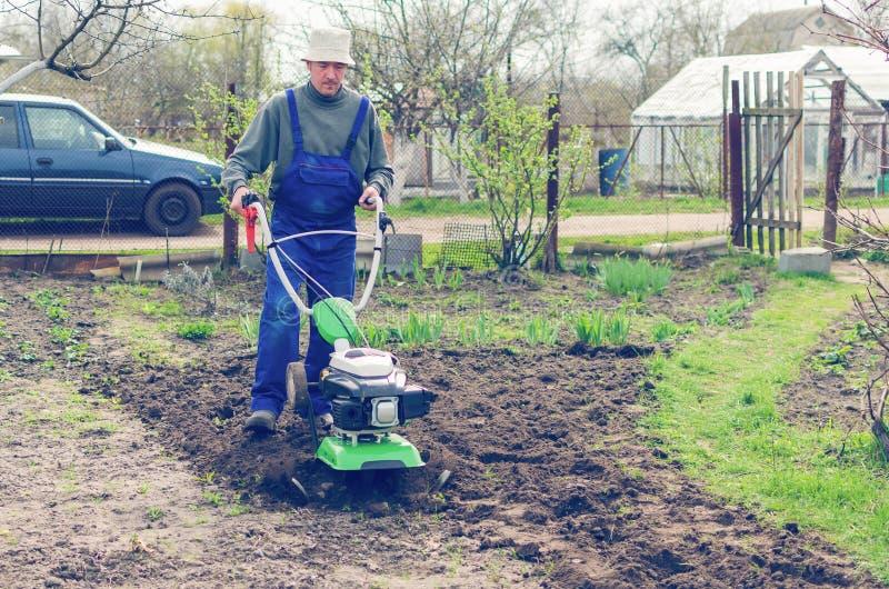 在春天有翻土机机器的庭院供以人员工作 库存照片