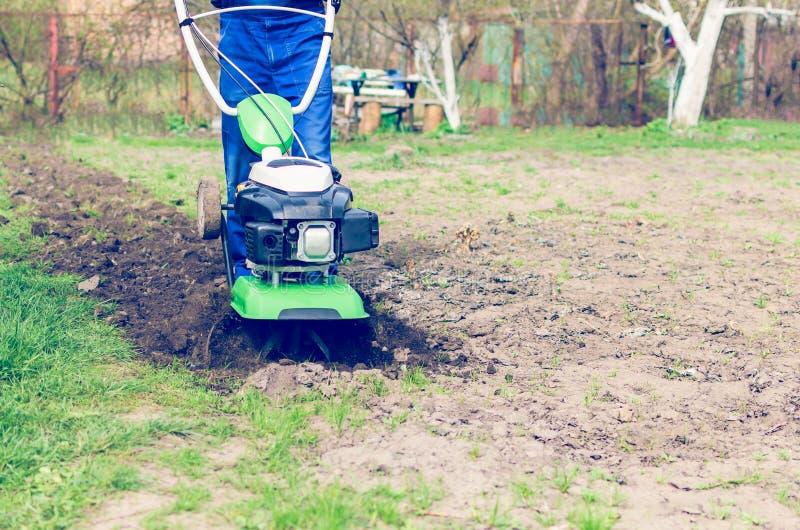 在春天有翻土机机器的庭院供以人员工作 免版税图库摄影