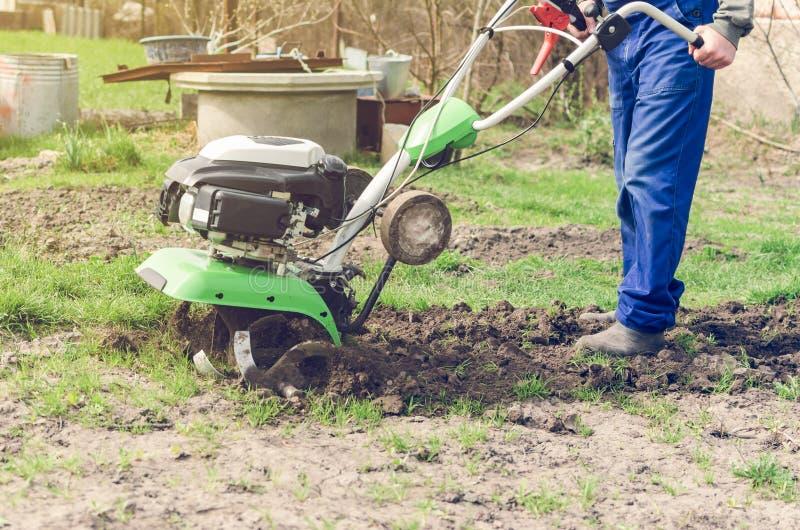 在春天有翻土机机器的庭院供以人员工作 免版税库存照片