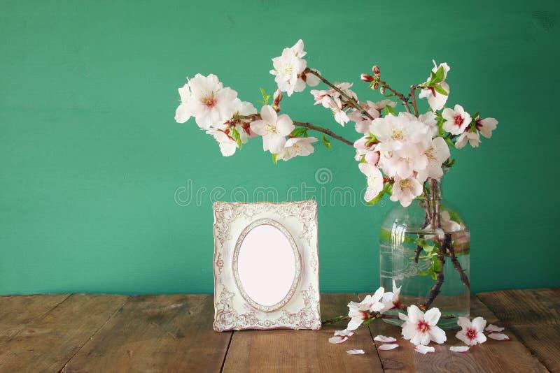 在春天白花旁边的葡萄酒空白的照片框架 库存照片