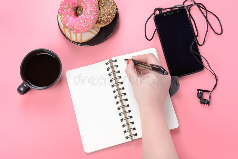 在春天的一个笔记本有棕色页的基于桃红色背景 妇女的手写道 在那里笔记薄附近 免版税库存照片