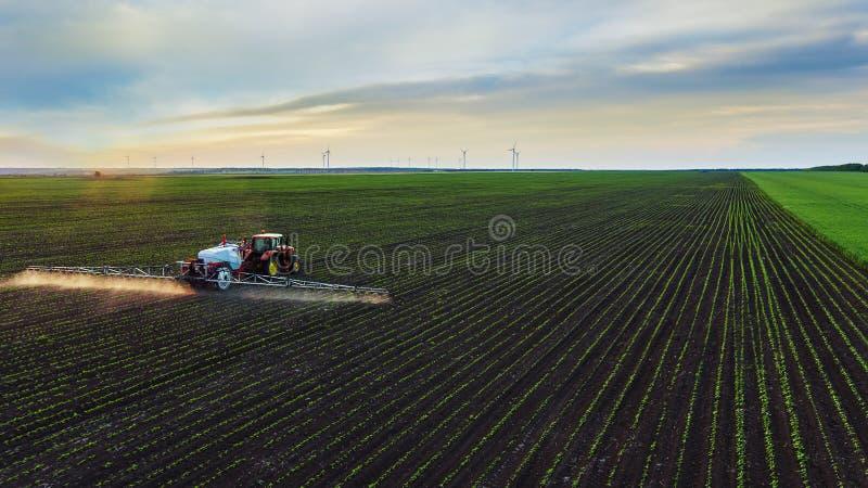 在春天的拖拉机喷洒的领域 库存照片