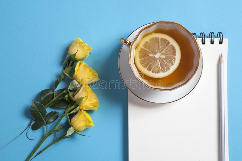 在春天的方形的笔记薄有白色牛皮纸的,铅笔、黄色玫瑰和茶在蓝色背景 免版税库存照片