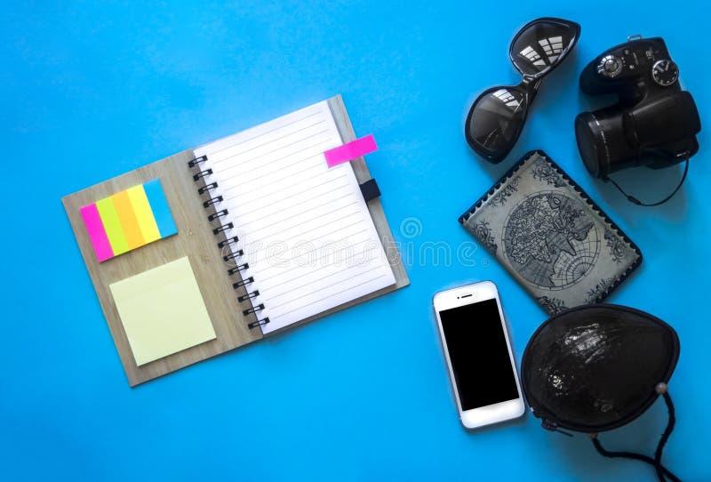 在春天的蓝色背景笔记本注意贴纸色的旁边玻璃袋子提包电话智能手机妇女护照地图照相机 库存图片