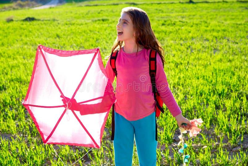 在春天草甸哄骗拿着桃红色风筝的女孩 免版税库存照片
