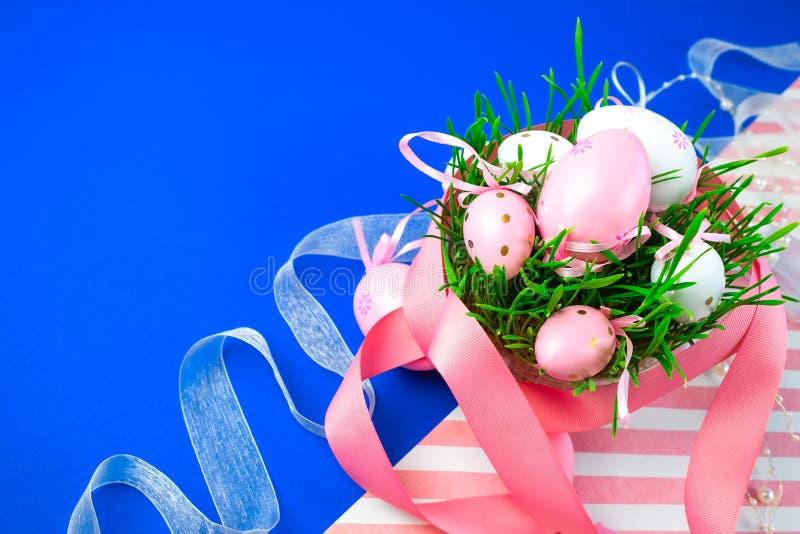 在春天草的复活节彩蛋用桃红色丝带装饰的复活节蓝色背景 库存图片