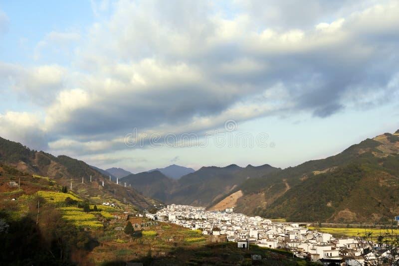 在春天,卷云通过山的村庄滚动 库存照片