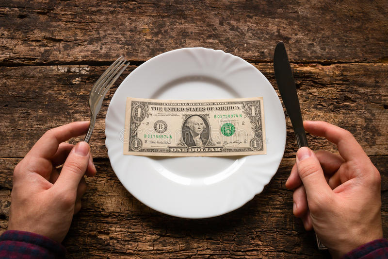 在是一美元的板材旁边供以人员拿着刀子和叉子 免版税库存图片