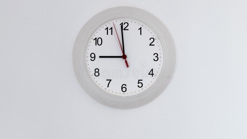 在显示九个小时的墙壁上的时钟 库存照片