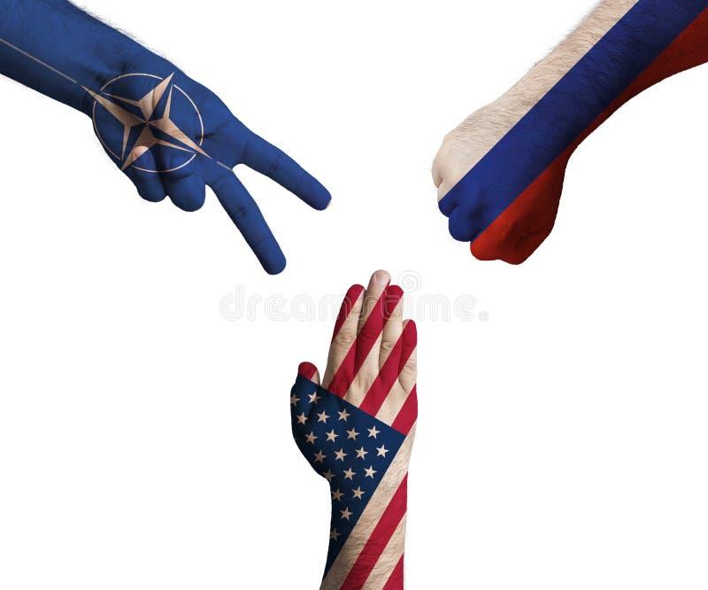 在显示剪刀,纸,石头的北约、美利坚合众国和俄罗斯联邦旗子装饰的手  免版税库存照片