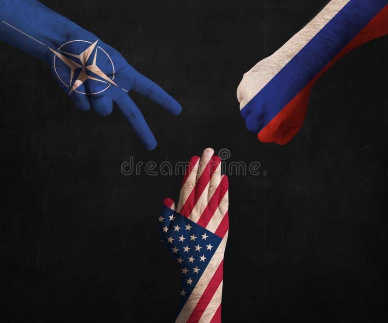 在显示剪刀,纸,石头的北约、美利坚合众国和俄罗斯联邦旗子装饰的手  库存图片