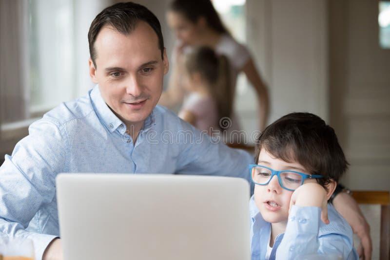 在显示器的父亲和儿子观看的录影在家 免版税库存图片