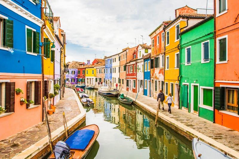 在显示明亮地被绘的房子和小船有反射的典型的街道场面的看法沿运河 免版税库存照片