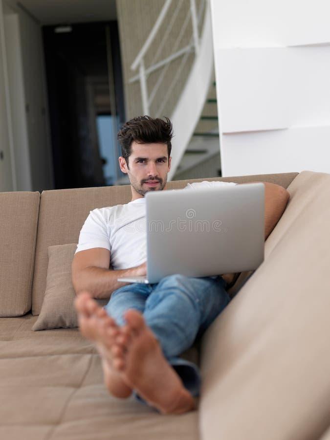 在显示曝光之上他的查看的膝上型计算机lcd人精密松弛肩膀沙发 图库摄影