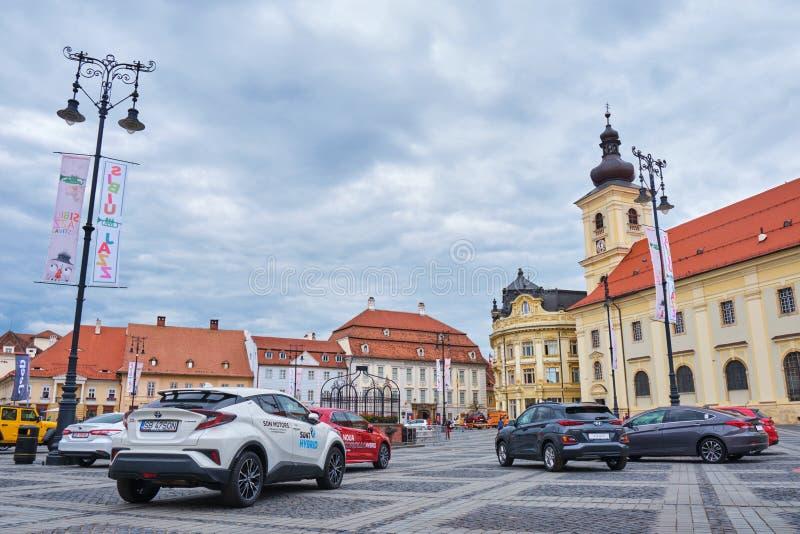 在显示的丰田和现代汽车在大正方形在锡比乌,罗马尼亚,在与风雨如磐的云彩的一阴天 库存照片