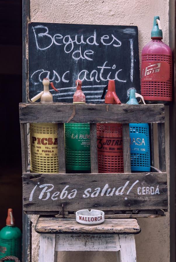 在显示的五颜六色的葡萄酒苏打瓶在一家酒店的一个土气木板箱与读老镇的签到加泰罗尼亚语 免版税图库摄影