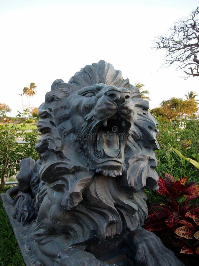 在显示的黑自然石咆哮狮子在庭院里 库存照片