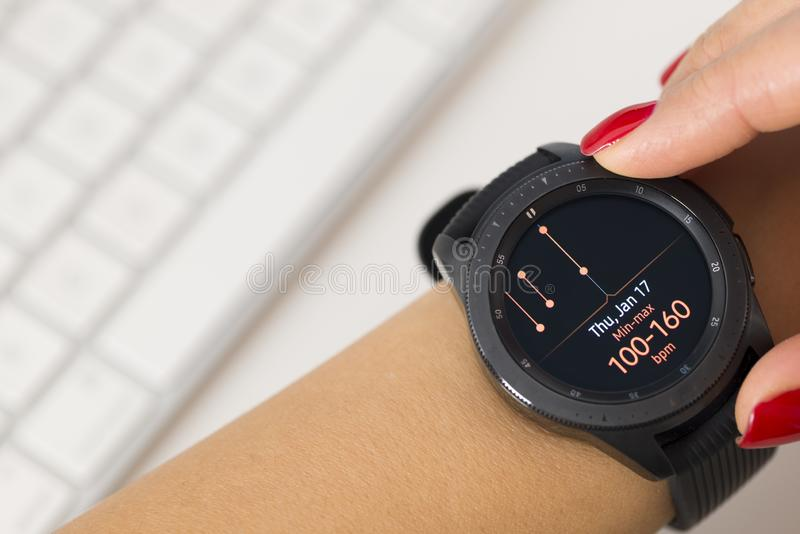 在显示被烧的卡路里的woman's手的便携的巧妙的手表 免版税图库摄影